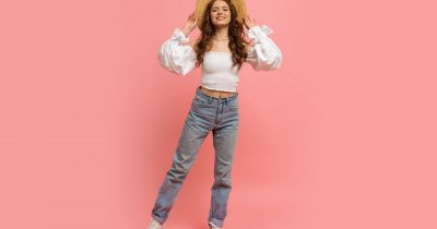 Full lenght image of Ppayful  woman in elegant linen top with balloon sleeves  and blue jeans posing on pink background.  Summer fashion trends.